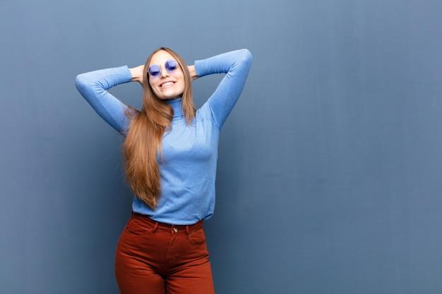 Jeune jolie femme avec des lunettes de soleil contre un mur bleu avec un espace de copie Photo Premium
