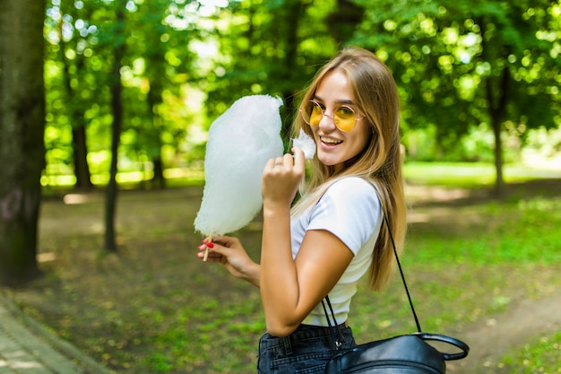 Jeune Jolie Femme Mangeant Une Barbe à Papa Dans Le Parc Photo gratuit