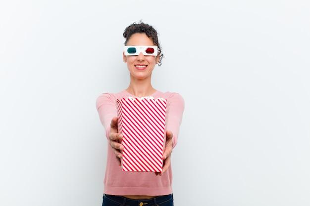 Jeune jolie femme avec des pop corn et des lunettes 3d contre blanc Photo Premium