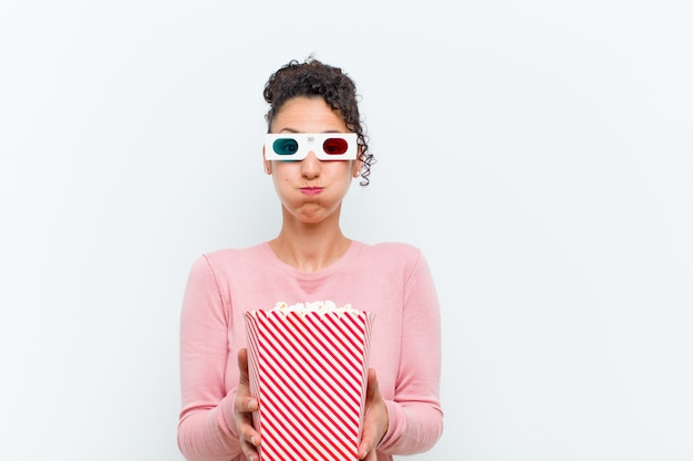 Jeune jolie femme avec des pop corn et des lunettes 3d contre un mur blanc Photo Premium