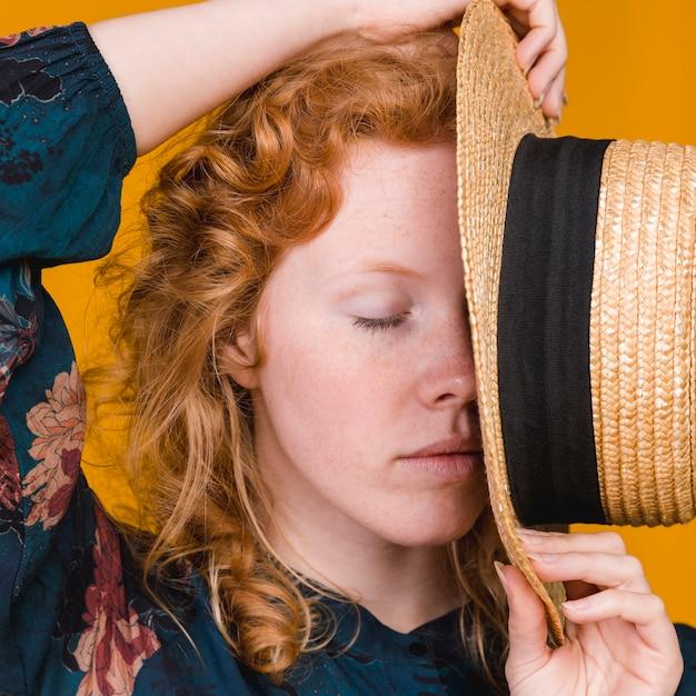 Jeune jolie femme posant avec un chapeau couvrant le visage Photo gratuit