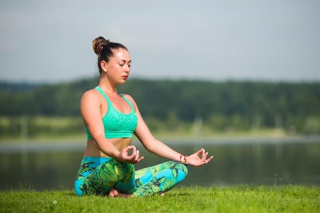 Jeune Jolie Femme En Posture De Lotus Dans Le Parc Photo gratuit