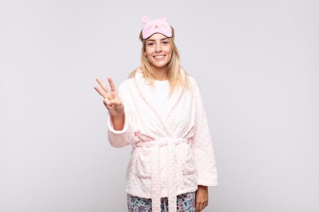 Jeune Jolie Femme En Pyjama, Souriant Et à La Recherche Amicale, Montrant Le Numéro Trois Ou Troisième Photo Premium
