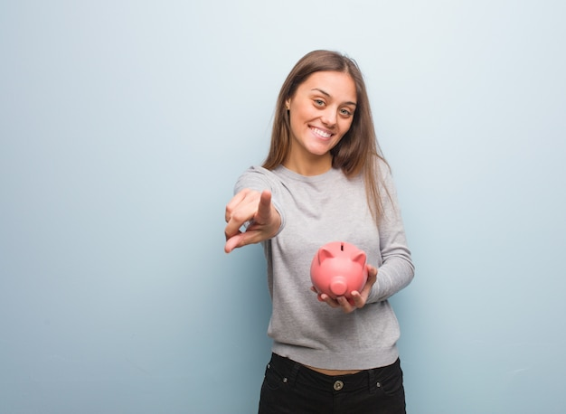Jeune jolie femme de race blanche gaie et souriante, pointant vers l'avant. elle tient une tirelire. Photo Premium