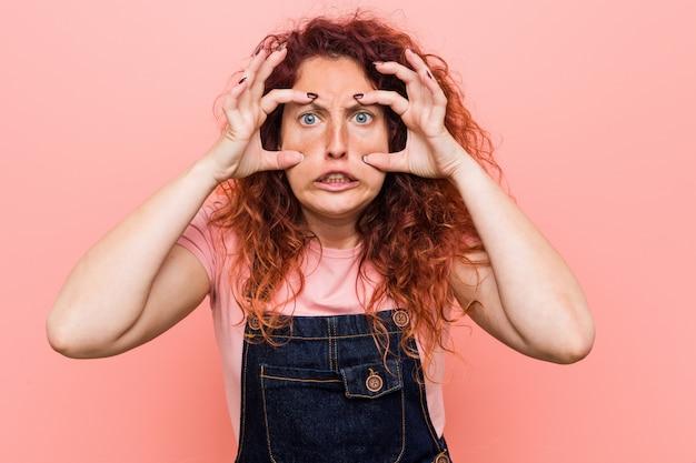 Jeune et jolie femme rousse au gingembre vêtue d'un salopette en jeans, gardant les yeux ouverts pour trouver une occasion de réussir. Photo Premium