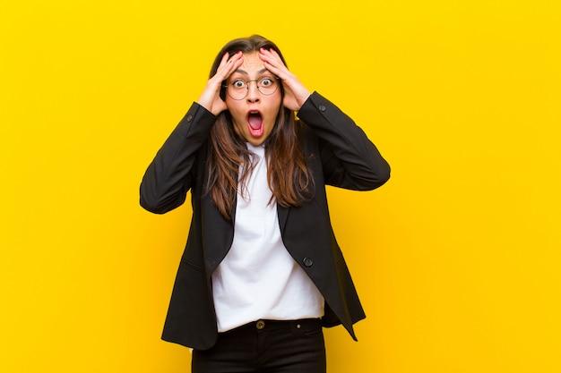 Jeune jolie femme se sentant horrifiée et choquée, levant les mains pour se diriger et paniquant face à une erreur contre le mur orange Photo Premium