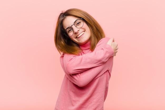 Jeune, Jolie Femme, Sentiment, Amoureux, Sourire, Câlins, Et, étreindre, Rester Célibataire, être égoïste Et égocentrique Sur Le Mur Rose Photo Premium
