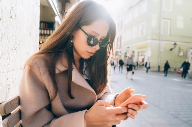 Jeune jolie femme avec un smartphone dans la rue Photo gratuit