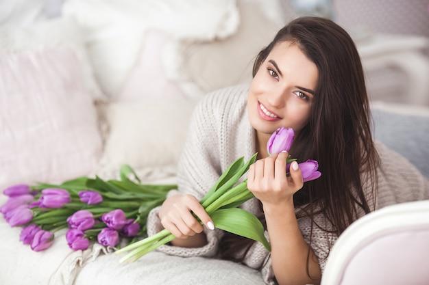 Jeune Jolie Femme Tenant Des Fleurs. Belle Dame Aux Tulipes Se Trouvant Sur Le Lit Photo Premium