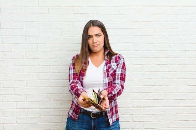 Jeune jolie femme avec une texture de mur de brique de portefeuille Photo Premium