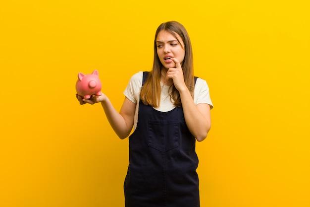Jeune jolie femme avec une tirelire sur fond orange Photo Premium