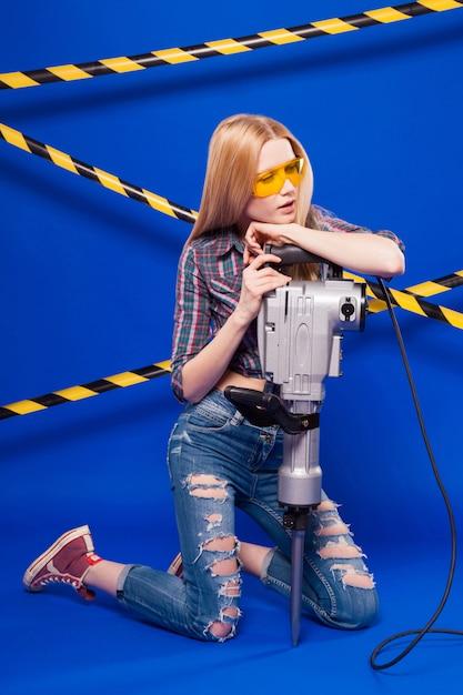 Jeune jolie fille de bâtisseur en chemise à carreaux, jeans et lunettes tiennent le perforateur Photo Premium