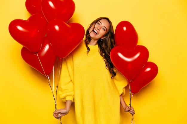 Jeune jolie fille avec long cheveux bouclés, en chandail jaune tenant des ballons à air rouge Photo gratuit