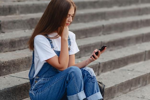 Jeune Jolie Fille Avec Mallette Assis Dans Les Escaliers Et écrit Sms Sur Téléphone Photo Premium