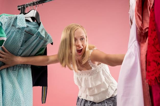 La Jeune Jolie Fille Regardant Les Robes Et L'essaie Tout En Choisissant Au Magasin Photo gratuit