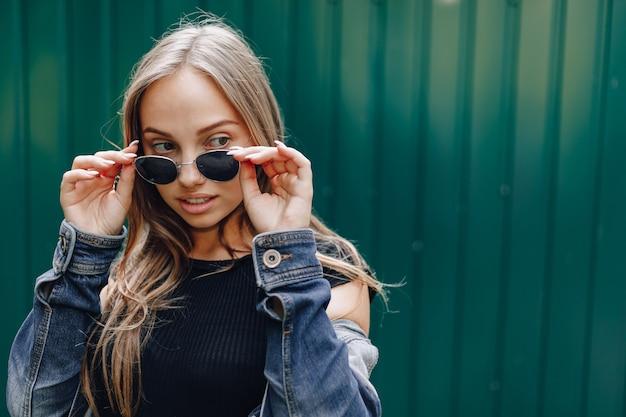 Jeune Jolie Fille Séduisante En Vêtements En Jean Dans Des Verres Sur Un Simple Fond Vert Foncé Avec Une Place Vide Pour Le Texte Photo gratuit