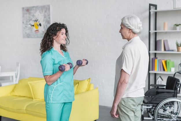 Jeune jolie infirmière aidant la vieille femme dans sa thérapie avec des haltères Photo gratuit