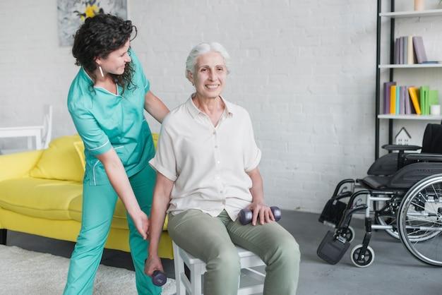 Jeune jolie infirmière aidant la vieille femme dans sa thérapie Photo gratuit