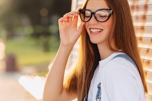 Jeune jolie jolie fille positive dans des lunettes élégantes au soleil du matin Photo Premium