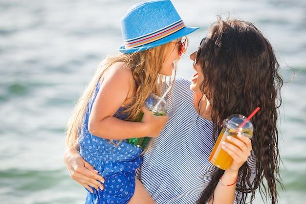Jeune Jolie Mère Et Sa Petite Fille Sur La Plage S'amusant Photo Premium