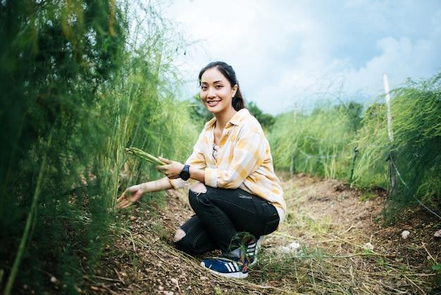 Jeune jolie paysanne récolte des asperges fraîches avec la main dans le champ. Photo gratuit