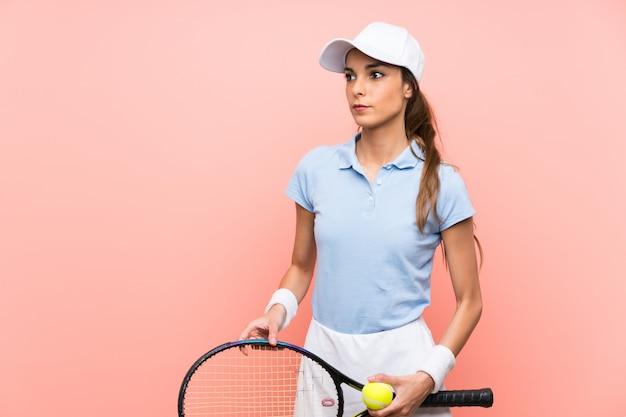 Jeune joueuse de tennis sur mur rose isolé Photo Premium
