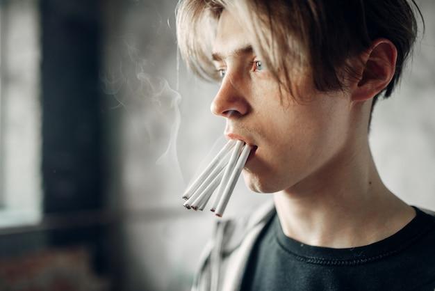 Jeune Junkie Avec De Nombreuses Cigarettes Dans Sa Bouche Photo Premium