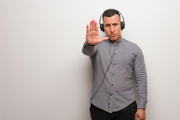 Jeune, Latin, Homme, écoute, Musique, Mettre, Main, Devant Photo Premium