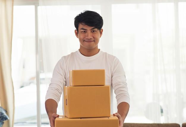 Jeune livreur logistique souriant tenant la boîte Photo gratuit