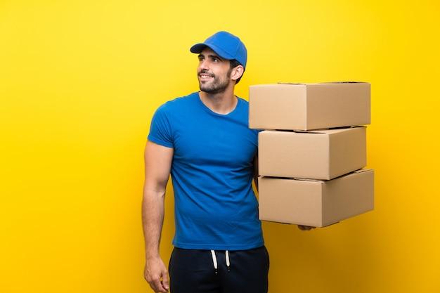 Jeune livreur sur un mur jaune isolé, levant en souriant Photo Premium