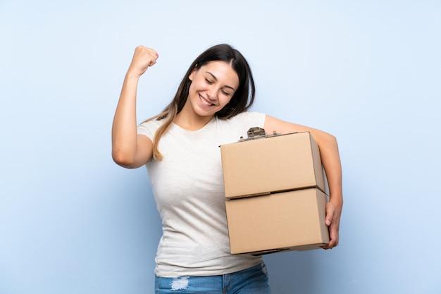 Jeune livreuse sur un mur de briques bleu célébrant une victoire Photo Premium