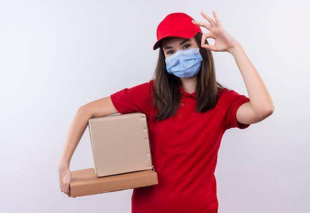 Jeune Livreuse Portant Un T-shirt Rouge à Bonnet Rouge Porte Un Masque Tenant Une Boîte Et Une Boîte à Pizza Montre Un Geste Correct Sur Fond Blanc Isolé Photo gratuit