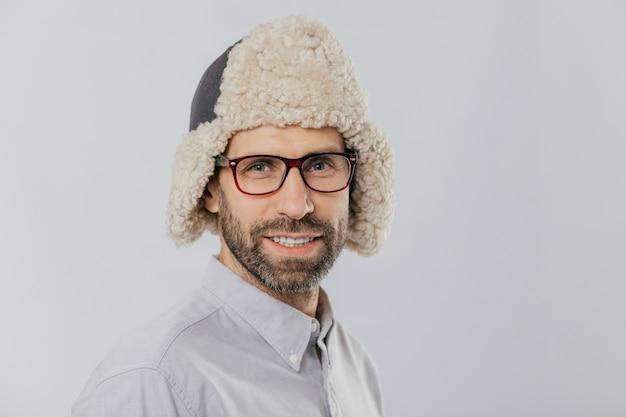 Jeune mâle d'apparence agréable, porte un chapeau futé chaud, des lunettes transparentes, des modèles sur un mur de studio blanc Photo Premium