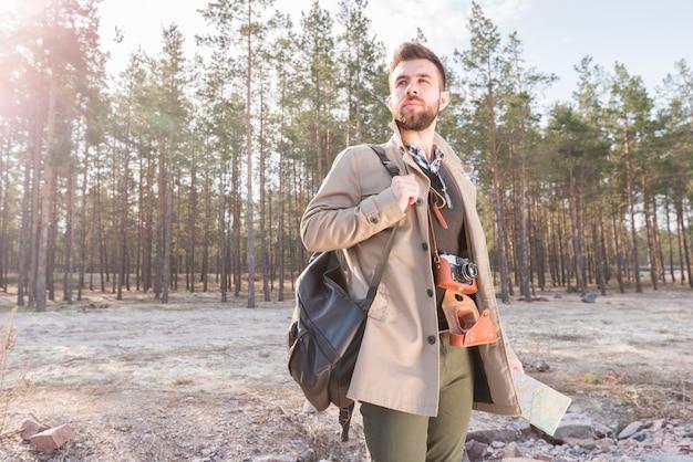 Jeune, mâle, voyageur, tenue, sac à dos, épaule, carte, debout, forêt Photo gratuit