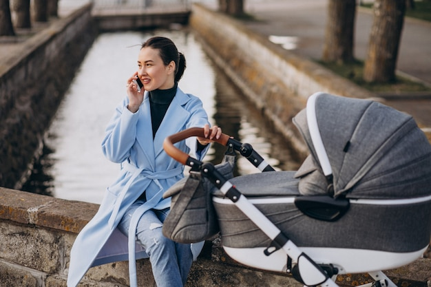 Jeune maman assise avec landau dans le parc Photo gratuit