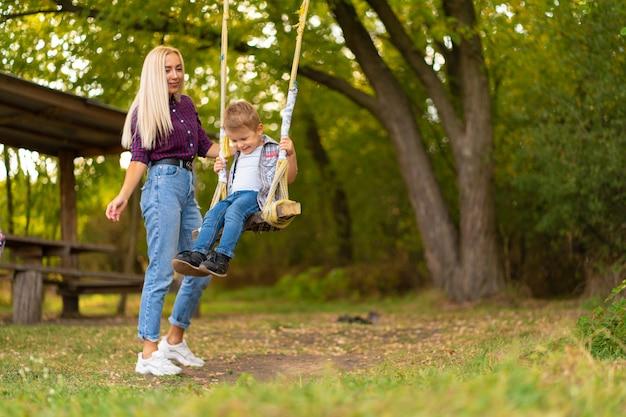 Jeune Maman Blonde Secoue Son Petit Fils Sur Une Balançoire Dans Un Parc Verdoyant. Enfance Heureuse. Photo Premium