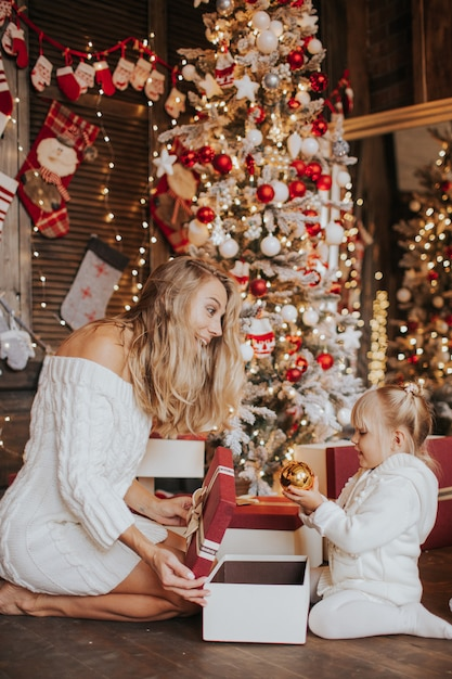 Jeune Maman Blonde Et Ses Filles En Vêtements Tricotés Blancs Ouvrant Un Cadeau De Noël Magique Par Un Arbre De Noël Dans Un Salon Confortable En Hiver Photo Premium