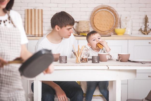 Jeune Maman Debout Devant Sa Famille Dans La Cuisine. Héhé, Dîner Ou Petit Déjeuner. Femme Faisant Le Dîner Pour Son Mari Et Son Petit Bébé. Photo Premium