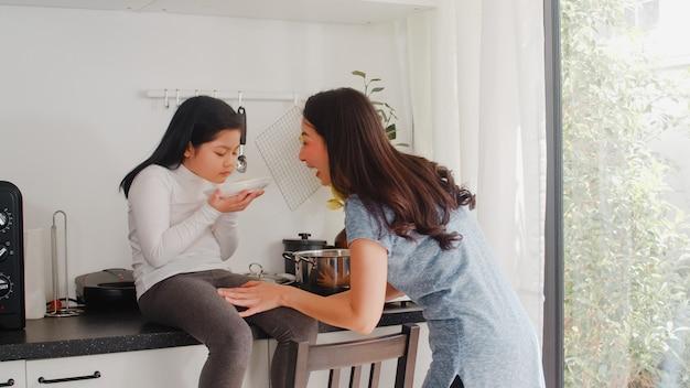 Jeune maman et fille japonaise asiatiques cuisinant à la maison. femmes de style de vie heureux faire des pâtes et des spaghettis ensemble pour le petit déjeuner dans la cuisine moderne à la maison le matin. Photo gratuit