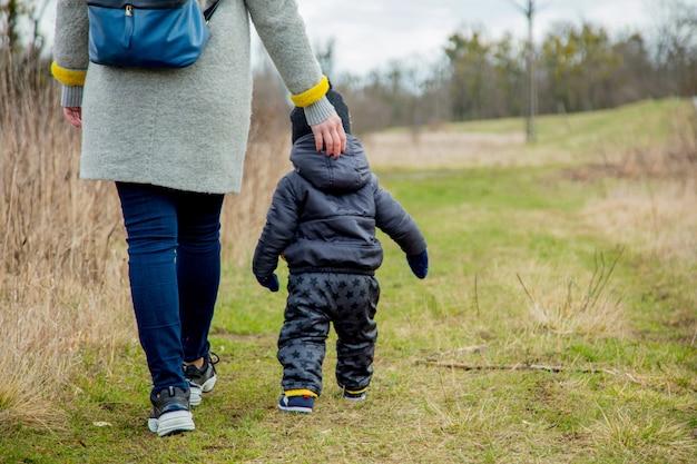 Jeune maman avec garçon d'enfant en bas âge à l'extérieur. Photo Premium