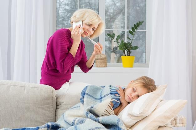 Jeune maman inquiète appelant médecin mesurant la température de sa fille. Photo Premium