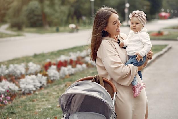 Jeune maman marchant dans un parc en automne avec calèche Photo gratuit