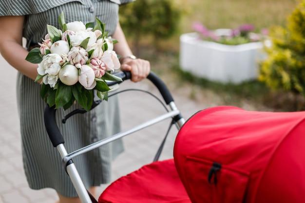 Jeune Maman Marche Avec Une Poussette Rouge Et Tient Dans Ses Mains Un Bouquet Original De Fleurs, D'oignons Et D'ail Photo Premium