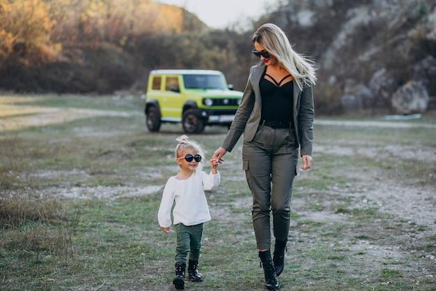Jeune maman avec une petite fille mignonne dans un parc en voiture Photo gratuit