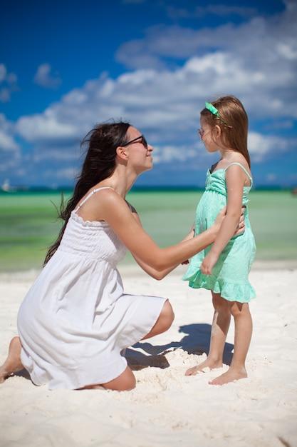 Jeune maman et sa fille mignonne s'amusent sur la plage exotique Photo Premium