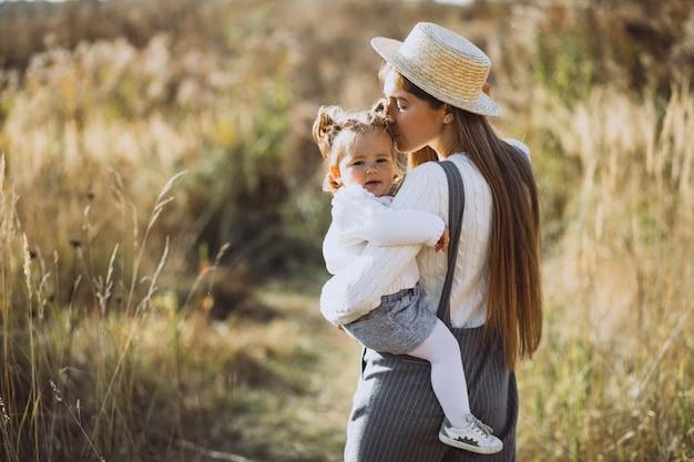 Jeune maman avec sa petite fille dans un champ d'automne Photo gratuit