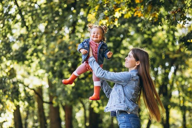 Jeune maman avec sa petite fille dans un parc en automne Photo gratuit