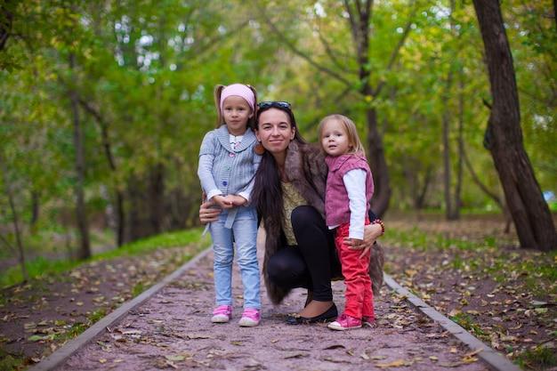 Jeune maman avec ses petites filles à la recherche d'une caméra oudoor Photo Premium