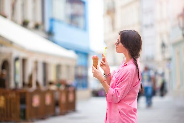 Jeune mannequin mangeant un cornet de crème glacée à l'extérieur. concept d'été - femme avec une glace douce au chaud Photo Premium