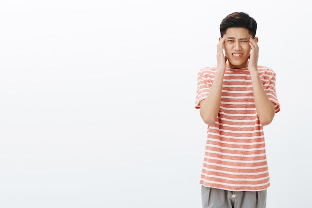 Jeune Mec Asiatique Inquiet En T-shirt Rayé Se Sentant Pressé Et Fatigué Se Tenant La Main Sur Les Tempes, Souffrant De Maux De Tête Ou De Migraine Photo gratuit